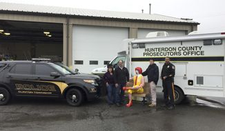 In this undated photo released by the Hunterdon County Prosecutor's Office, Detective Dean Cerdeira, second from right, of the Hunterdon County Prosecutor's Office, and Detective Thomas Hash, right, of the Clinton Township Police Department, pose with a recovered Ronald McDonald statue along with Diane, left, and Phillip Koury, the owners of the statue, in Clinton, N.J. Hunterdon County prosecutors say the 250-pound fiberglass statue of the clown character sitting on a bench was taken from the McDonald's in Clinton. They announced Friday, May 5, 2017, that it had been found but declined further comment. (Paul Approvato/Hunterdon County Prosecutor's Office via AP)