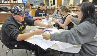 ADVANCE FOR WEEKEND EDITIONS, MAY 6-8 - In this April 26, 2017 photo, Pepsimen group members fashion prototype products out of repurposed plastic for Lautenbach Industries during an innovation STEM project at Sedro-Woolley High School in Sedro-Woolley, Wash.. In the foreground, Dominik Rico, left, cuts a piece for plastic rope with help from Denisse Lopez, right,. Behind, from left, Jared Schmidt, Logan Gustafson, Richard Ershig and Alexandra Anderson make prototype camping pads. (Scott Terrell/Skagit Valley Herald via AP)