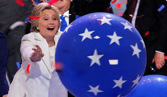 Then-presidential nominee Hillary Clinton reaches for a falling balloon at the conclusion of the 2016 Democratic National Convention in Philadelphia. (Associated Press) ** FILE **