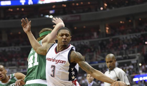 Washington Wizards guard Bradley Beal (3) dribbles past Boston Celtics center Kelly Olynyk (41), of Canada, and Avery Bradley (0) during the first half in Game 4 of a second-round NBA basketball playoff series, Sunday, May 7, 2017, in Washington. (AP Photo/Nick Wass)