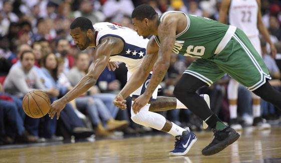 Washington Wizards guard John Wall, left, fights for the ball against Boston Celtics guard Marcus Smart, right, during the second half in Game 4 of a second-round NBA basketball playoff series, Sunday, May 7, 2017, in Washington. (AP Photo/Nick Wass)