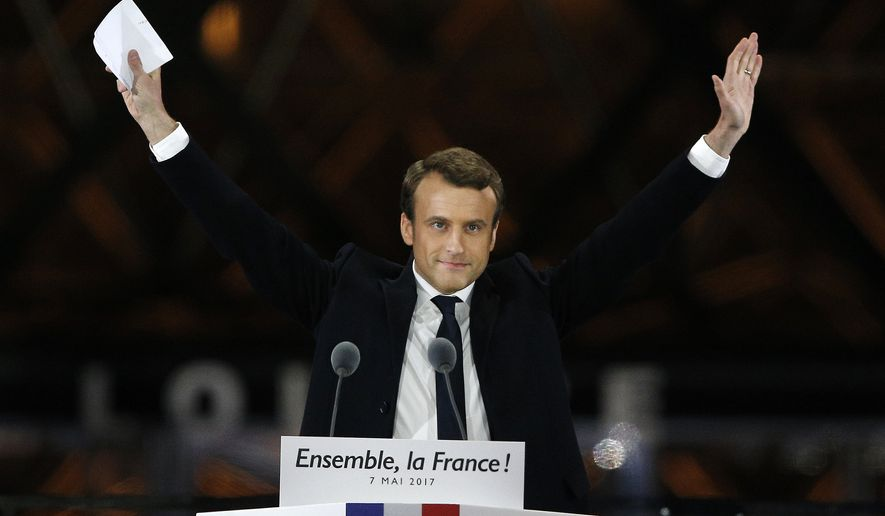 "French President-elect Emmanuel Macron gestures during a victory celebration outside the Louvre museum in Paris, France, Sunday, May 7, 2017. Speaking to thousands of supporters from the Louvre Museum's courtyard, Macron said that France is facing an ""immense task"" to rebuild European unity, fix the economy and ensure security against extremist threats. (AP Photo/Thibault Camus)"