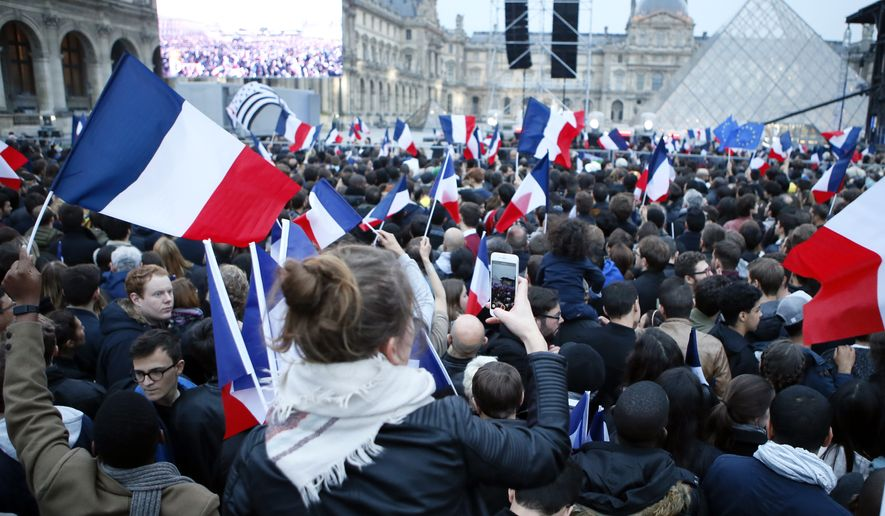 People wave French flags at the Louvre museum where Emmanuel Macron is planning to celebrate, Sunday, May 7, 2017 in Paris.Thousands of supporters of French centrist candidate Emmanuel Macron have let out a big cheer when national television called the presidential election in his favor based on poll projections. (AP Photo/Francois Mori)