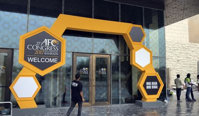 A member of staff walks towards the building hosting the AFC, Asian Football Confederation Congress 2017, in Manama, Bahrain, Sunday, May 7, 2017. The specter of fresh corruption scandals hangs over the annual gathering of world soccer leaders, two years after the FIFA Congress was shaken by the exposure of far-reaching fraud. The election of Asian members to FIFA's ruling council on Monday kickstarts a week of meetings in Bahrain, with powerbroker Sheikh Ahmad Al Fahad Al Sabah off the ballot after his alleged bribery was disclosed by American authorities. (AP Photo/Rob Harris)