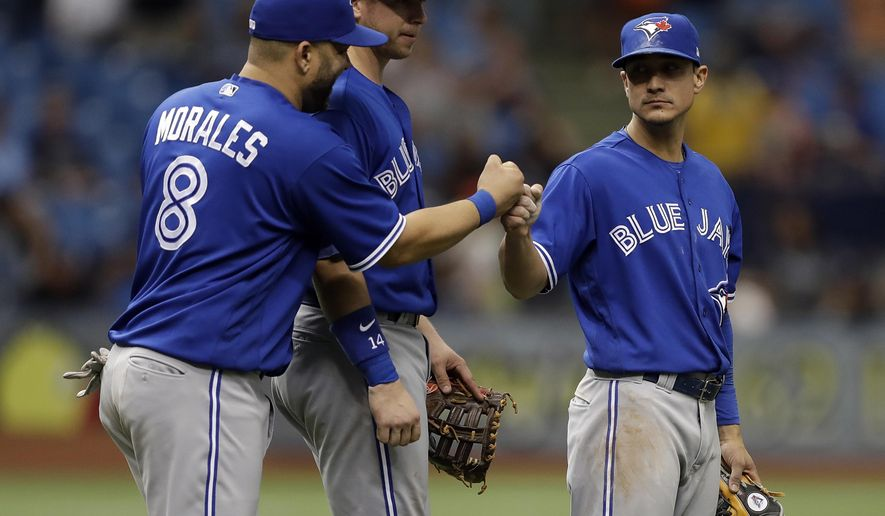 Toronto Blue Jays' Darwin Barney, right, celebrates with teammates Kendrys Morales, left, and Justin Smoak, center, after they defeated the Tampa Bay Rays in a baseball game Sunday, May 7, 2017, in St. Petersburg, Fla. (AP Photo/Chris O'Meara)