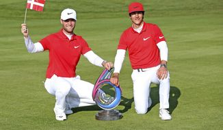 Denmark's Thorbjorn Olesen, right, and Lucas Bjerregaard celebrate with the trophy after the winning the final during day two of the Golf Sixes at the Centurion Club, St Albans England,Sunday May 7, 2017. (Steven Paston/PA via AP)