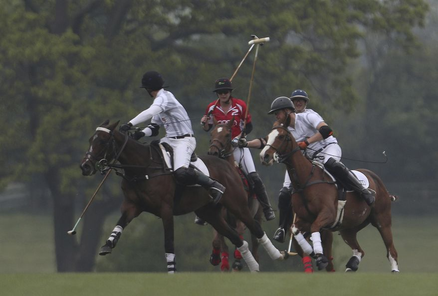 Britain's Prince Harry, on horse at right, takes part in the annual Audi Polo Challenge at Coworth Park polo club in Ascot, Berkshire, England, Saturday, May 6, 2017. (Steve Parsons/PA via AP)