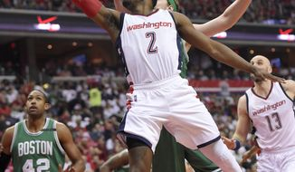 Washington Wizards guard John Wall (2) goes to the basket against Boston Celtics center Al Horford (42), of Dominican Republic, and Kelly Olynyk, back center, of Canada, during the first half in Game 4 of a second-round NBA basketball playoff series, Sunday, May 7, 2017, in Washington. (AP Photo/Nick Wass)