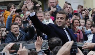 French independent centrist presidential candidate Emmanuel Macron waves as he leaves the polling station after casting his ballot in the presidential runoff election in Le Touquet, France, Sunday, May 7, 2017. Voters across France are choosing a new president in an unusually tense and important election that could decide Europe's future, making a stark choice between pro-business progressive candidate Emmanuel Macron and far-right populist Marine Le Pen. (AP Photo/Christophe Ena)