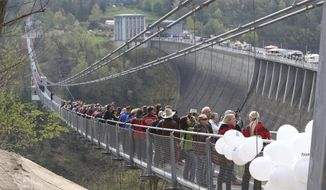 People walk across the newly opened cable suspension bridge at the Rappbode dam near Ruebeland, Germany, Sunday, May 7, 2017. According to the operators, the bridge is the longest pedestrian cable suspension bridge in the world. (Matthias Bein/dpa via AP)