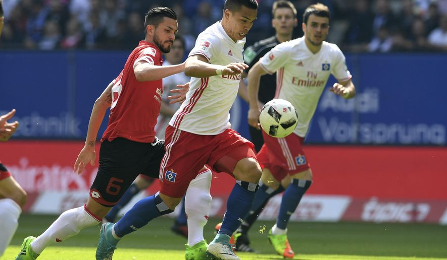Hamburg's Bobby Wood, right, and Mainz's Danny Latza, left, challenge for the ball during a German first division Bundesliga soccer match between Hamburger SV and FSV Mainz in Hamburg, northern Germany, Sunday, May 7, 2017.  (Carmen Jaspersen/dpa via AP)