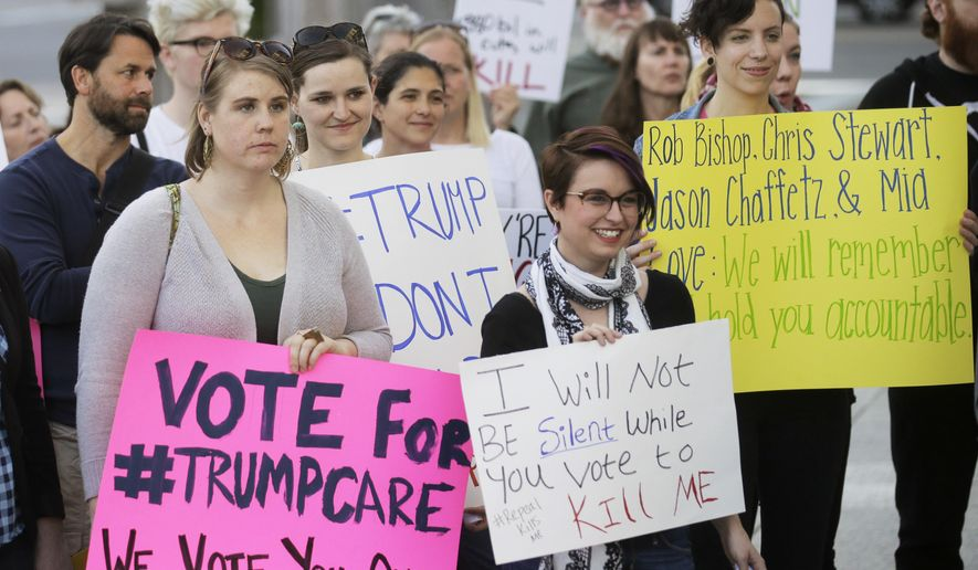 FILE - In this Thursday, May 4, 2017 file photo, demonstrators hold signs during a healthcare rally in Salt Lake City. Utah's all-Republican House delegation voted Thursday in favor of a health care overhaul that could impact people with pre-existing conditions, triggering serious worries from people who fit that category. (AP Photo/Rick Bowmer)