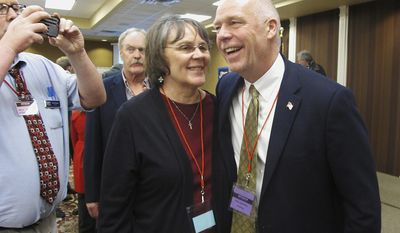 FILE - In this March 6, 2017, file photo, Greg Gianforte, right, receives congratulations from a supporter in Helena, Mont., after winning the Republican nomination for Montana's special election for the U.S. House. The technology entrepreneur's substantial wealth has become a focus in the May 25 special congressional election. Democrat Rob Quist and Libertarian Mark Wicks are also vying to become Montana's sole representative in the U.S. House. (AP Photo/Matt Volz, File)