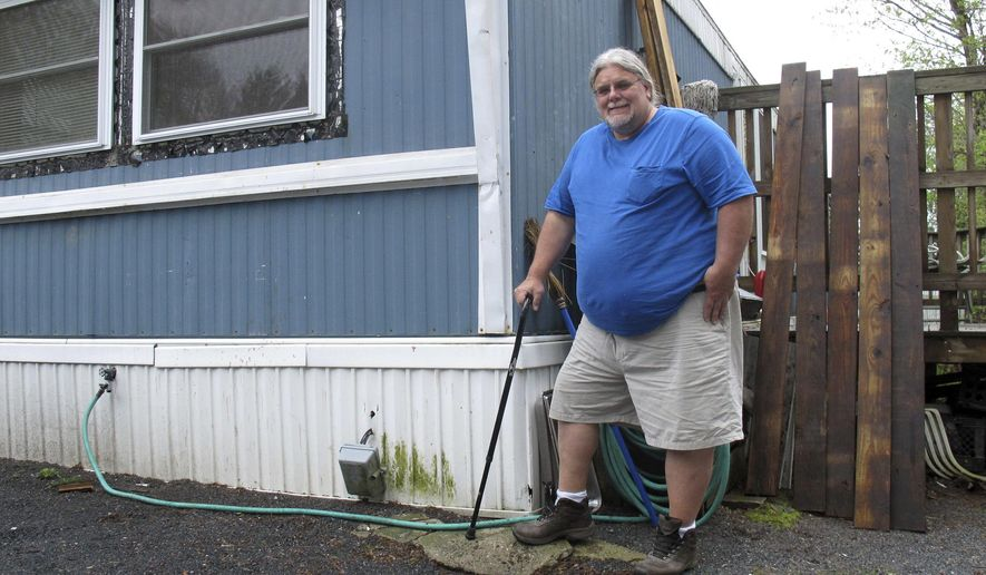 In this Tuesday May 2, 2017 photo, Todd Alexander poses at his mobile home in Milton, Vt., that he heats with the help of the Low Income Heating Home Energy Assistance Program. Alexander, who is disabled and living on disability, said the assistance has helped him meet his energy needs and still have money left over to live. Congress overruled a request by President Donald Trump to eliminate the heating assistance program. (AP Photo/Wilson Ring)