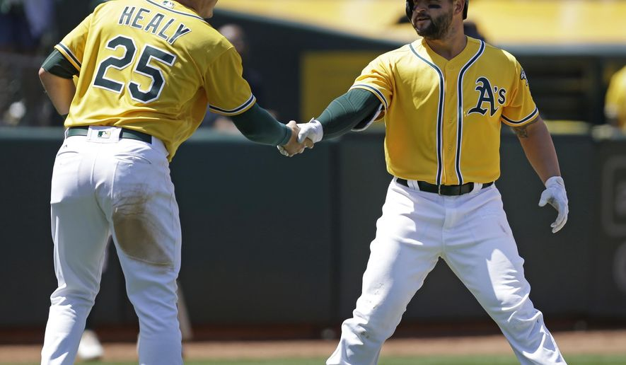 Oakland Athletics' Yonder Alonso, right, celebrates with Ryon Healy (25) after hitting a two run home run off Detroit Tigers' Daniel Norris in the fourth inning of a baseball game, Sunday, May 7, 2017, in Oakland, Calif. (AP Photo/Ben Margot)