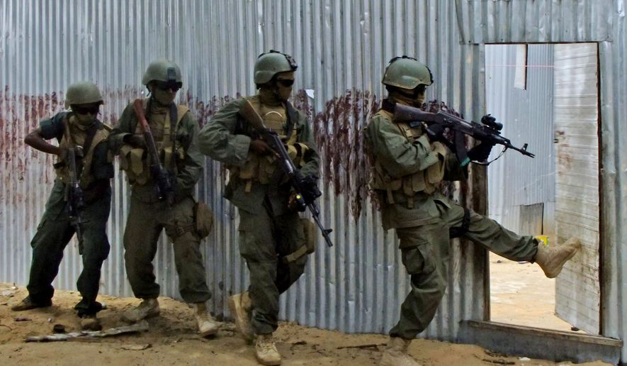 Masked Somali national army (SNA) soldiers search through homes for al-Shabaab fighters during an operation in Ealsha Biyaha, Somalia, on June, 2, 2012. (Associated Press) **FILE**