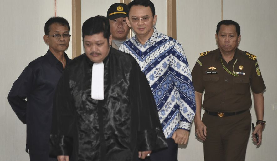 """Jakarta Gov. Basuki """"Ahok"""" Tjahaja Purnama, center, is escorted by prosecutors as enters the court room for his sentencing hearing in Jakarta, Indonesia, Tuesday, May 9, 2017. The minority Christian governor is currently on trial on accusation of blasphemy following his remark about a passage in the Quran that could be interpreted as prohibiting Muslims from accepting non-Muslims as leaders. (Bay Ismoyo/Pool Photo via AP)"""
