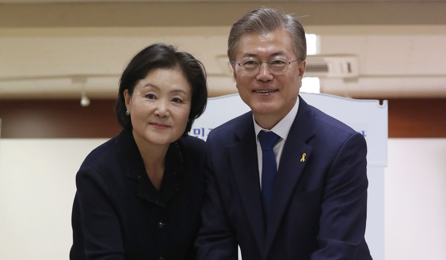 South Korean presidential candidate Moon Jae-in of the Democratic Party and his wife Kim Jung-suk prepare to cast their ballot for a presidential election at a junior high school in Seoul, South Korea, Tuesday, May 9, 2017. South Koreans voted Tuesday for a new president, with victory widely predicted for a liberal candidate who has pledged to improve ties with North Korea, re-examine a contentious U.S. missile defense shield and push sweeping economic changes. (Jeon Heon-kyun/Pool Photo via AP)