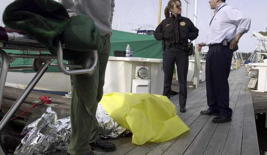 In this Feb. 28, 2004, photo, Sausalito police officer B. Baraz, back left, and then-Coroner Investigator Darrell Harris, right, prepare to move a body found at the yacht harbor in Sausalito, Calif. Harris has been arrested and charged with sexually abusing a girl younger than 14. He is scheduled to be arraigned Monday, May 8, 2107, on four felony charges and a misdemeanor count of sexually abusing the girl over the last nine years. (Jeff Vendsel/Marin Independent Journal via AP)