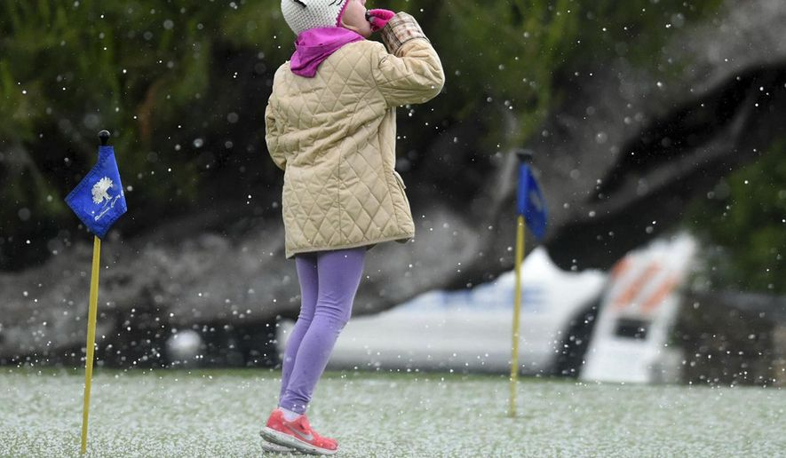 Mackenzie VandenBosch, 6, of Redlands, Calif., puts a piece of hail in her mouth during a spring storm that hit Southern California with gusty winds, thunderstorms and pea-size hail Sunday, May 7, 2017. (John Valenzuela/Los Angeles Daily News via AP)