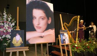 FILE - In this May 28, 2002 pool-file photo taken at the Modesto Centre Plaza in Modesto, Calif., photos of Chandra Levy are on display as musicians, right, stand by at the memorial service for Levy. Ingmar Guandique, a Salvadoran national, whose conviction in the slaying Levy was overturned has been deported. Immigration and Customs Enforcement (ICE) officials said Guandique was flown Friday, May 5, 2017, to San Salvador and transferred to authorities there. (AP Photo/Debbie Noda, Pool, File)