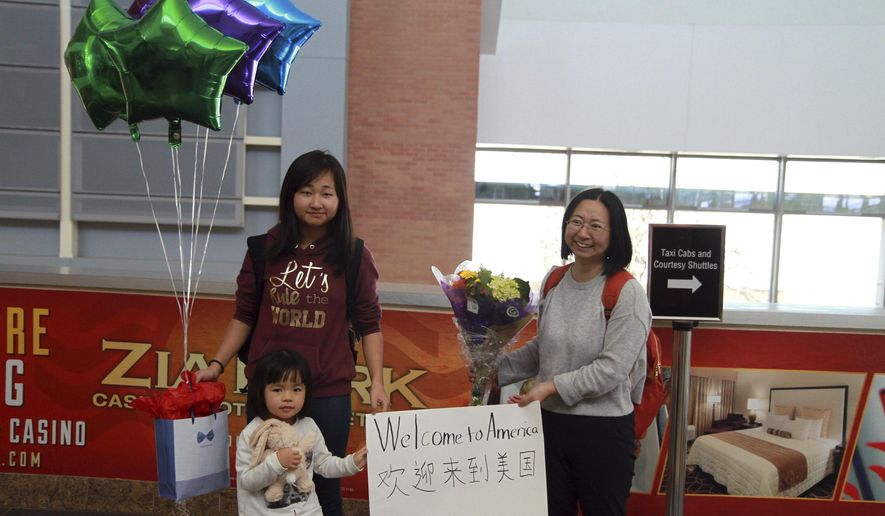 """In this March 17, 2017, photo and released by China Aid, Chen Guiqiu, right, holds a """"Welcome to America"""" sign with her daughters Xie Yajuan, 15, and Xie Yuchen, 4, after arriving at an airport in Texas. Chen whose husband, prominent rights lawyer Xie Yang, is held on charge of inciting subversion made a harrowing flight from China with her daughters chased by Chinese security agents across Southeast Asia. (China Aid via AP)"""