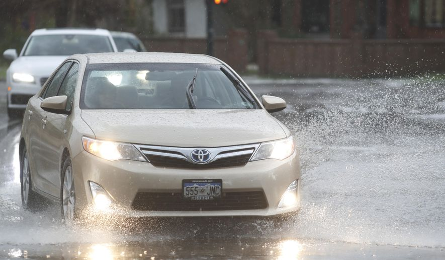 A motorist guides his car through a puddle along Speer Boulevard as a spring storm, packing high winds, heavy rains and hail, sweeps over Colorado's Front Range just before the afternoon rush hour Monday, May 8, 2017, in Denver. (AP Photo/David Zalubowski)