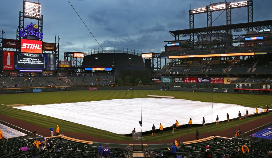 Coors Field grounds crew pull the tarp back on the field before the delayed start of a baseball game between the Chicago Cubs and Colorado Rockies, Monday, May 8, 2017, in Denver. (AP Photo/ Jack Dempsey)