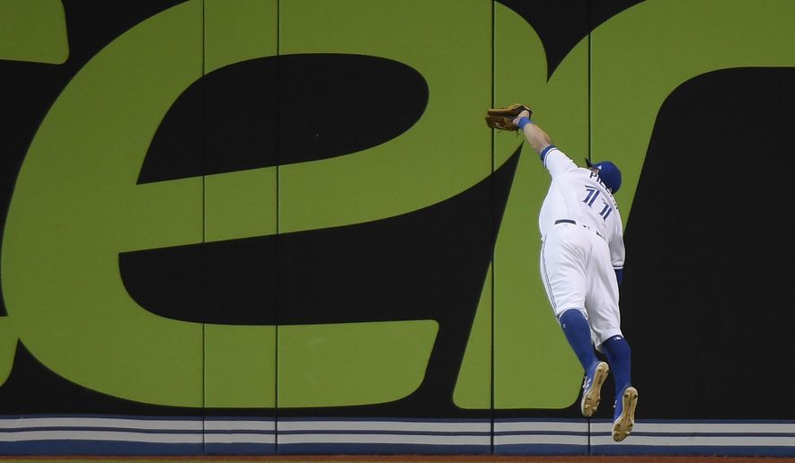 Toronto Blue Jays center fielder Kevin Pillar (11) makes a diving catch on Cleveland Indians' Jose Ramirez during the sixth inning of a baseball game in Toronto on Monday, May 8, 2017. (Nathan Denette/The Canadian Press via AP)