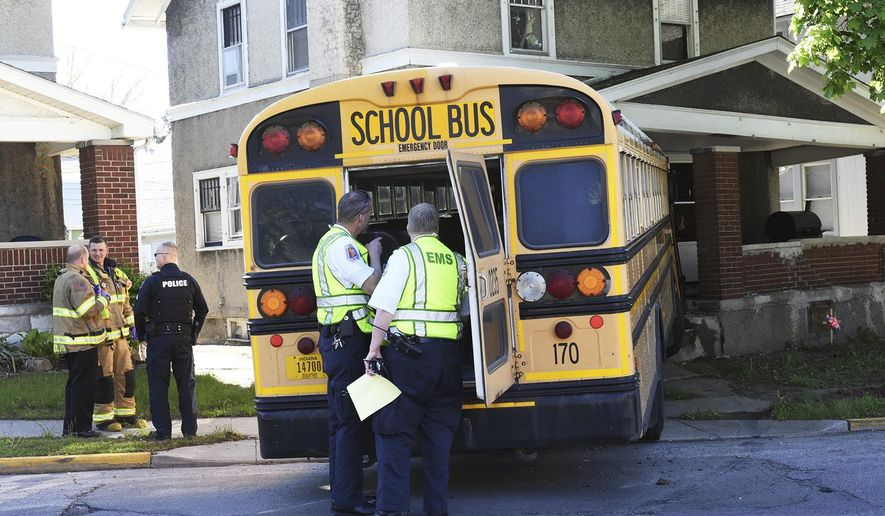 Rescue workers investigate at the scene where a Fort Wayne Community Schools bus ran into a home in Fort Wayne, Ind., Monday morning May 8, 2017. WANE-TV reported no students were aboard the bus when it collided with another vehicle and hit the home. (Cathie Rowand/The Journal-Gazette via AP)