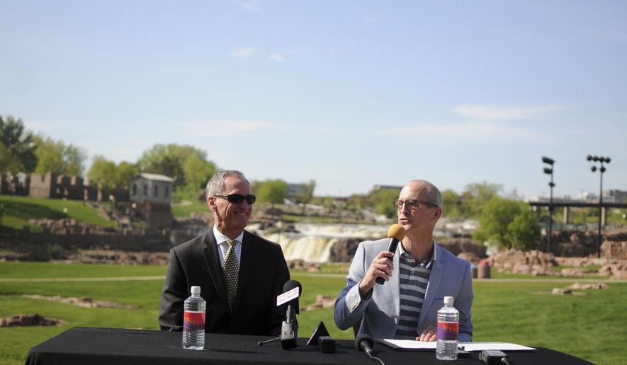 Gov. Dennis Daugaard, left, and Tourism Secretary Jim Hagen, right, hold a tourism event in Sioux Falls, S.D., Monday, May 8, 2017. Officials say they're hopeful for a strong summer tourism season even without major anniversaries that have been a big draw for visitors in recent years. (AP Photo/James Nord)