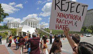 Protesters hold signs and march in front of the State Capitol across the street from the US 4th Circuit Court of Appeals in Richmond, Va., Monday, May 8, 2017. The court will examine a ruling that blocks the administration from temporarily barring new visas for citizens of Iran, Libya, Somalia, Sudan, Syria and Yemen. It's the first time an appeals court will hear arguments on the revised travel ban, which is likely destined for the U.S. Supreme Court.(AP Photo/Steve Helber)