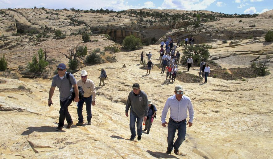 Utah state legislators and their staff lead the way for Interior Secretary Ryan Zinke, Utah Gov. Gary Herbert and others in the distance Monday, May 8, 2017, through Bears Ears National Monument near Blanding, Utah. Zinke says he wants to make sure Native American cultural standing is preserved in a new national monument but cautioned that not all tribal members share the same opinion about it. (AP Photo/Michelle Price)