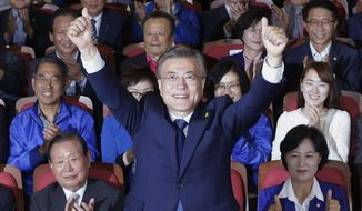 South Korea's presidential candidate Moon Jae-in of the Democratic Party raises his hands as his party leaders and members watch on television local media's results of exit polls for the presidential election in Seoul, South Korea, Tuesday, May 9, 2017. Exit polls forecast that liberal candidate Moon will win the election Tuesday to succeed ousted President Park Geun-hye. Official results weren't expected for hours, but the exit poll of about 89,000 voters at 330 polling stations, jointly commissioned by three major television stations and released just after polls closed, showed Moon receiving 41.4 percent of the vote. (AP Photo/Ahn Young-joon)