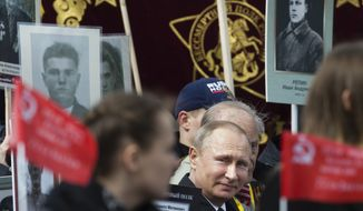 Russian President Vladimir Putin, center, walks among other people carrying portraits of relatives who fought in World War II, with Russian and Soviet flags, during the Immortal Regiment march at the Red Square in Moscow, Russia, on Tuesday, May 9, 2017, celebrating 72 years since the end of WWII and the defeat of Nazi Germany. (AP Photo/Ivan Sekretarev)