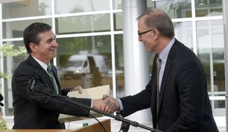 North Carolina Gov. Roy Cooper, left, and Wilson Ervin, Chair of the Credit Suisse Americas Foundation exchange, shake hands during a news conference at Credit Suisse in Morrisville, N.C., Tuesday, May 9, 2017. Credit Suisse plans to add up to 1,200 jobs at its North Carolina technology hub. The jobs projection comes five weeks after North Carolina partially repealed a state law limiting LGBT rights. (AP Photo/Gerry Broome)