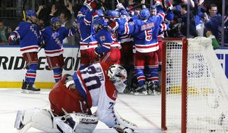 FILE - In this May 13, 2015, file photo, the New York Rangers celebrate the game winning goal by center Derek Stepan (21) against the Washington Capitals as Capitals goalie Braden Holtby looks at the puck in the net in overtime of Game 7 of the Eastern Conference semifinals during the NHL hockey Stanley Cup playoffs in New York. Game 7 may be the most exciting phrase in sports to a lot of people, but not the Washington Capitals. The Capitals have lost six of nine times they've faced Game 7 in the Alex Ovechkin era. Wednesday, May 10, 2017 is the chance for the Capitals to confront its Game 7 demons as it hosts the defending Stanley Cup champion Pittsburgh Penguins. (AP Photo/Kathy Willens, File)