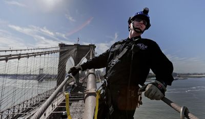 In this Tuesday, May 2, 2017, New York Police detective Slawek Dziubek turns to check on fellow Emergency Services Unit officers during a training exercise climb up the south cable of the Brooklyn Bridge, in New York. The New York Police Department's Emergency Services Unit is an elite team that handles the city's most dangerous rescues. The 400-officer unit is among the most highly-trained in the nation and is the most coveted assignment at the nation's largest department. (AP Photo/Julie Jacobson)