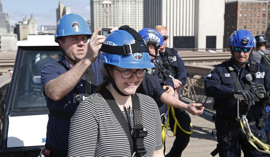 In this Tuesday, May 2, 2017 photo, Associated Press video journalist Ted Shaffrey, left, attaches a miniature camera to a helmet worn by Associated Press reporter Colleen Long, center, before the pair climbed the Brooklyn Bridge with an AP photographer and New York Police Department's elite officers who execute the most difficult rescues, including those on bridges and skyscrapers, in New York. The police officers demonstrated their high-rise rescue skills for the three AP journalists in an exclusive outing scaling the bridge's suspension cables. (AP Photo/Seth Wenig)