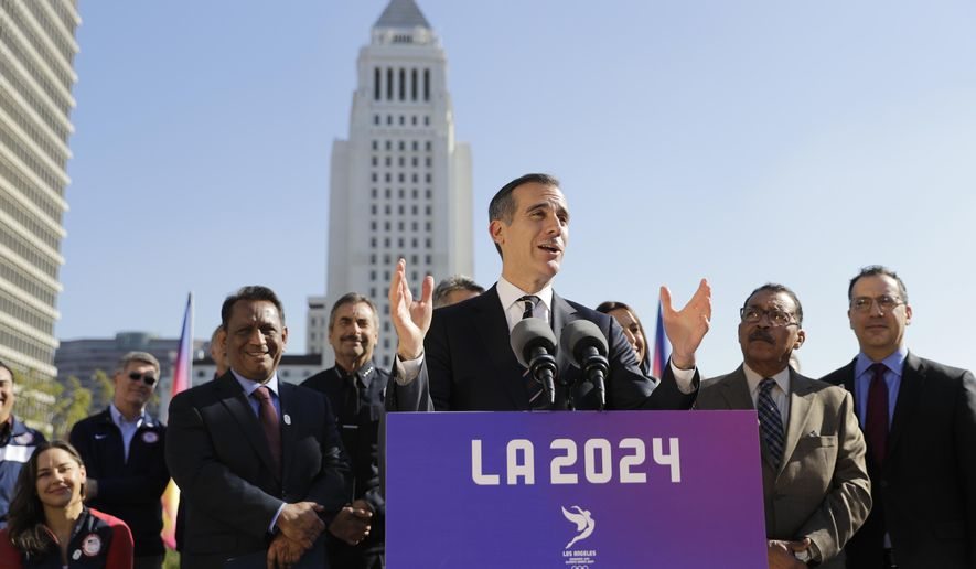 FILE - In this Jan. 25, 2017, file photo, Los Angeles Mayor Eric Garcetti, center, speaks during a news conference in Los Angeles. Los Angeles leaders this week are trying to sell their plan to host the Olympic Games to visiting members of the International Olympic Committee. (AP Photo/Jae C. Hong, File)