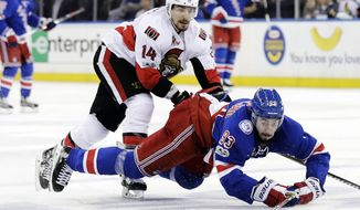 New York Rangers' Mika Zibanejad (93) and Ottawa Senators' Alex Burrows (14) fights for control of the puck during the second period of Game 6 of an NHL hockey Stanley Cup second-round playoff series Tuesday, May 9, 2017, in New York. (AP Photo/Frank Franklin II)