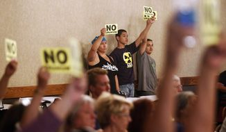 """In this Monday, May 8, 2017 photo, opponents to the Dewey-Burdock Uranium Mine near Edgemont, S.D., hold up """"NO URANIUM"""" signs during an Environmental Protection Agency hearing in Rapid City, S.D. Water quality is a major concern for opponents of the proposed southwest South Dakota uranium mine. (Chris Huber/Rapid City Journal via AP)"""
