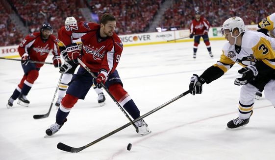 Washington Capitals center Evgeny Kuznetsov (92), from Russia, who lost his helemt, passes the puck past Pittsburgh Penguins defenseman Olli Maatta (3), from Finland, during the second period of Game 7 in an NHL hockey Stanley Cup Eastern Conference semifinal, Wednesday, May 10, 2017, in Washington. (AP Photo/Alex Brandon)