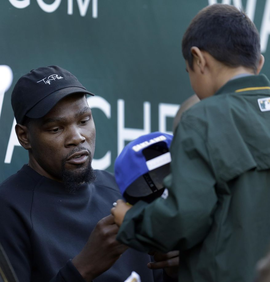Golden State Warriors' Kevin Durant signs an autograph during the first inning of a baseball game between the Los Angeles Angels and Oakland Athletics, Tuesday, May 9, 2017, in Oakland, Calif. (AP Photo/Ben Margot)