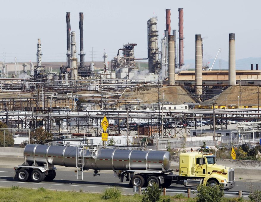 In this March 9, 2010, file photo, a tanker truck passes an oil refinery in Richmond, Calif. A measure that would impose a hefty tax on carbon pollution and use much of the revenue to give money back to taxpayers is scheduled for a hearing in a California state Senate committee Wednesday, May 10, 2017. (AP Photo/Paul Sakuma, File)