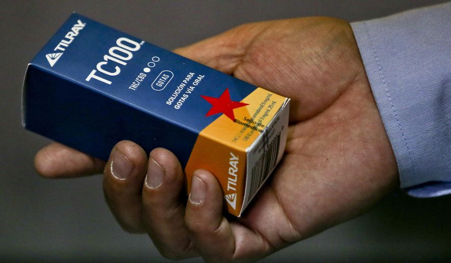 Pharmacist Jaime Lobo shows a box of TC100 drugs at one of the first two pharmacies in Latin America to sell cannabis sativa-based drugs in Santiago, Chile, Wednesday, May 10, 2017. The prescription drug made in Canada is to treat patients for chronic pain. (AP Photo/Esteban Felix)