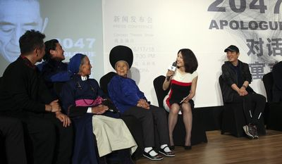 """In this Tuesday, May 9, 2017 photo, movie director Zhang Yimou, right, looks as an emcee speaks with the Chinese female folk art performers on stage during a press conference for the """"2047 Apologue"""" in Beijing. Zhang's new, much smaller-scale endeavor aims to start a conversation about the relationship between people and technology, and where this relationship is heading. He called """"2047 Apologue"""" a """"conceptual performance, because it's not a show or a story."""" Instead, he has hired Chinese folk art performers and companies from Europe and the U.S. to supply technology such as drones and robotic arms for the hourlong show that is broken into several """"fragments."""" It will be performed at the National Center for Performing Arts in Beijing from June 16-18, and then tour several Chinese cities. (AP Photo/Louise Watt)"""