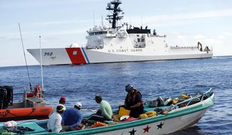In this Feb. 23, 2017 photo, a U.S. Coast Guard law enforcement team from the USCG cutter Stratton boards a small fishing boat that was stopped carrying close to 700 kilos of pure cocaine, in the Pacific Ocean hundreds of miles south of the Guatemala-El Salvador border. Hidden in the bales of cocaine was a GPS tracking device wrapped inside a condom, a sure sign the drug bosses behind the shipment knew right away it didn't reach its destination. (AP Photo/Dario Lopez-Mills)