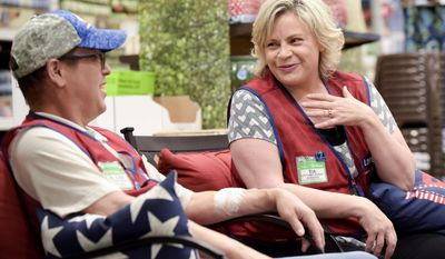 In this May 5, 2017 photo, Tia Hess, left, who will be donating her kidney to help Freddie Hale, her coworker at Lowe's, joke around in Nampa, Idaho. (Chris Bronson/The Idaho Press-Tribune via AP)