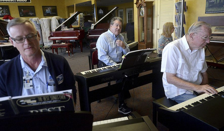 """ADVANCE FOR SUNDAY MAY 14 AND THEREAFTER  - In a Tuesday, April 25, 2017 photo. Robert Zoschke, center, joins in playing """"Memory"""" from the musical Cats as he teaches a group of adult students, including Joel Jones, left, Bill Graber, and Eve McCreary, at The Piano Center  in Beaumont, Texas. The group meets weekly for lessons, as well as a healthy dose of social time. Zoschke is now the last man standing for piano tuning and repair in Beaumont, having learned the trade from his father, Marvin Zoschke, who started the piano sales and service business on Eleventh Street in the 1950's. (Kim Brent/The Enterprise/The Beaumont Enterprise via AP)"""